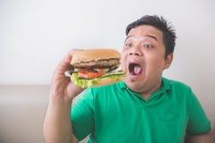 Overweight man eating hamburger at home Stock Photo