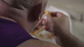 Overweight man eating takeaway pizza with appetite, unhealthy food, closeup. Stock footage stock footage