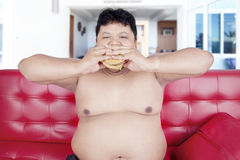 Overweight man eats burger on the couch. Image of hungry overweight person sitting on the sofa while eating burger with two hands at home Stock Images