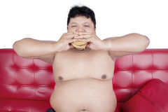 Overweight man eats burger with two hands. Portrait of overweight person feels hungry and eat a cheeseburger with two hands while sitting on the sofa Royalty Free Stock Photography