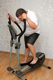 Overweight man exercising on trainer Royalty Free Stock Photography