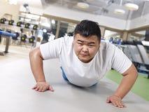 Overweight man exercising stock photo