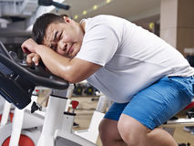 Overweight man exercising. An overweight young man exhausted with exercising in fitness center Royalty Free Stock Photography