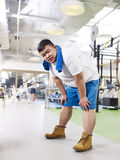 Overweight man exhausted in gym Stock Images
