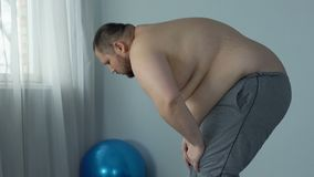 Overweight man feeling fatigue and breath disorder during home workout, dyspnea. Stock footage stock video