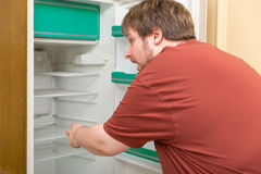 Overweight man in front of a empty fridge Royalty Free Stock Image