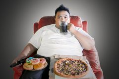Overweight man with junk foods during watch TV stock image
