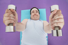 Overweight Man Lifting Dumbbells Royalty Free Stock Images