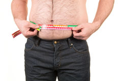 Overweight man measuring belly fat with measure tape. On a white background Royalty Free Stock Images