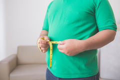 Overweight man measuring his belly at home Royalty Free Stock Photography