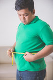 Overweight man measuring his belly at home Royalty Free Stock Images