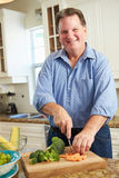 Overweight Man Preparing Vegetables in Kitchen Stock Photography