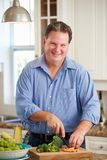 Overweight Man Preparing Vegetables in Kitchen Royalty Free Stock Image