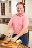 Overweight Man Preparing Vegetables in Kitchen Stock Image