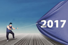 Overweight man pulling banner with 2017 Stock Image