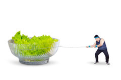 Overweight man pulling salad Royalty Free Stock Image