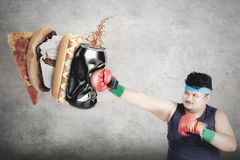 Overweight man punching junk foods Royalty Free Stock Photo