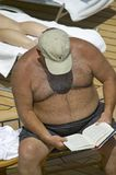 Overweight man reading book while laying in the sun Stock Photo