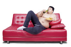 Overweight man reclining on couch Stock Image