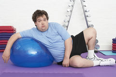 Overweight Man Resting On Exercise Ball Stock Photography