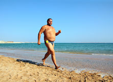 Overweight man running on beach Royalty Free Stock Photography