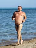 Overweight man running on beach Stock Photos