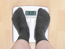 Overweight man on scales Stock Photography
