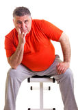 Overweight man sitting on a bench for abdominals, he takes a bre Royalty Free Stock Image