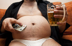 Overweight man sitting on the couch Stock Image