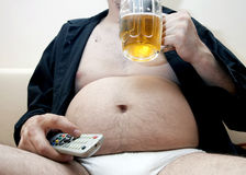 Overweight man sitting on the couch Royalty Free Stock Photos
