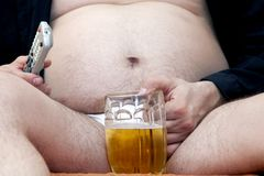 Overweight man sitting on the couch Stock Photo