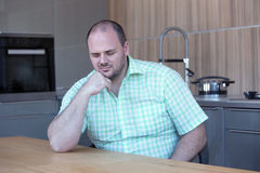 Overweight man sitting at kitchen table with eyes closed Stock Photo
