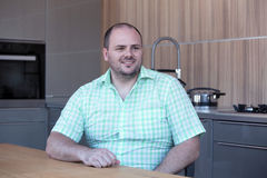 Overweight man sitting at kitchen table and smiles Stock Photos