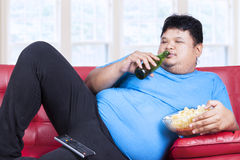 Overweight man sitting lazy on sofa. While drinking beer and eat snack Royalty Free Stock Photography