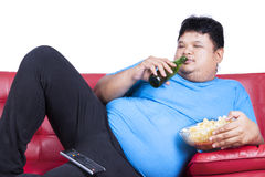 Overweight man sitting lazy on sofa 1. Overweight man sitting lazy on sofa while drinking beer and eat snack Stock Image