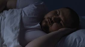 Overweight man sleeping in bed at night, resting on comfortable pillow, dreams. Stock footage stock footage