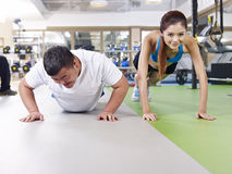 Overweight man and slim girl exercising together Stock Photos