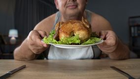Overweight man smelling greasy grilled chicken with enjoyment, unhealthy food Royalty Free Stock Images