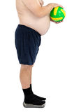 Overweight man stands on weight scales. With yellow-green ball Stock Images