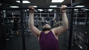 Overweight man trying to pull up on sport bar, weak body muscles, gym training
