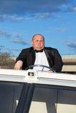 Overweight man in a tuxedo at the helm of a pleasure boat Stock Photo