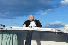Overweight man in a tuxedo at the helm of a pleasure boat Royalty Free Stock Image