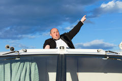 Overweight man in a tuxedo at the helm of a pleasure boat Stock Image