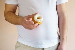 Overweight man with unhealthy fattening food. Fattening food, high-calorie snack. weight loss, dietary, balanced nutrition. overweight man eating unhealthy sweet stock images