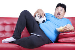 Overweight man watching football match 1. Overweight man sitting lazy on sofa while drinking beer and eat snack Stock Photography