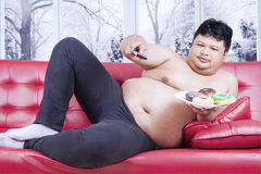 Overweight man watching tv and eats donuts. Overweight man watching television while eating donuts and sitting on the sofa in winter season Royalty Free Stock Images