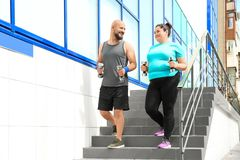 Overweight man and woman running with dumbbells. On stairs outdoors royalty free stock photo
