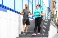 Overweight man and woman running with dumbbells stock photos