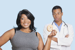 Overweight mixed race woman with donut by doctor over blue background Royalty Free Stock Photo