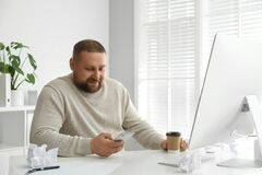 Free Overweight Office Employee With Smartphone At Workplace Royalty Free Stock Image - 181021326